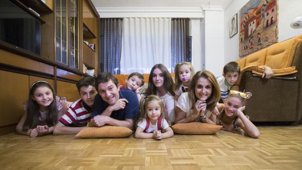 Un matrimonio y sus ocho hijos posan en el salón de su casa