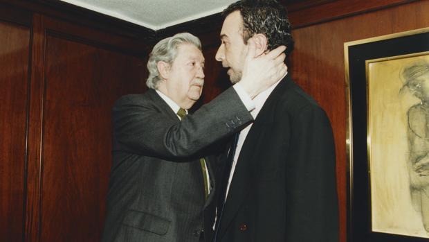 Manuel Alcántara abraza a José Luis Garci en 1998, durante la presentación del libro «Vuelta de hoja»