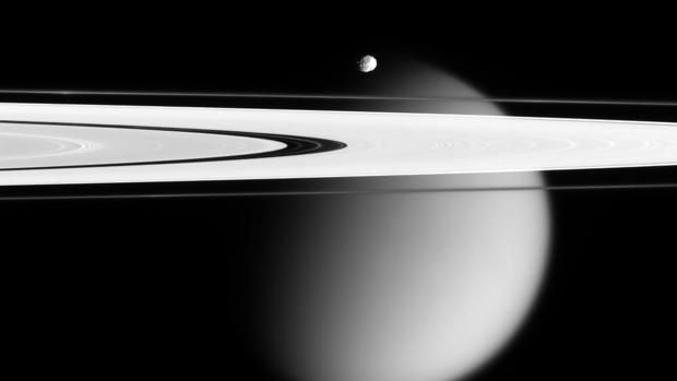 Vista de Epimeteo, luna menor de Saturno, sobre los anillos. Al fondo, Titán
