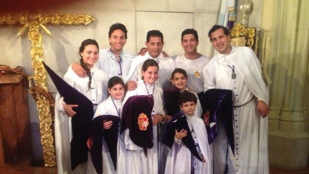 Oliva Soto vestido con la túnica de nazareno de los Gitanos acompañado por su familia