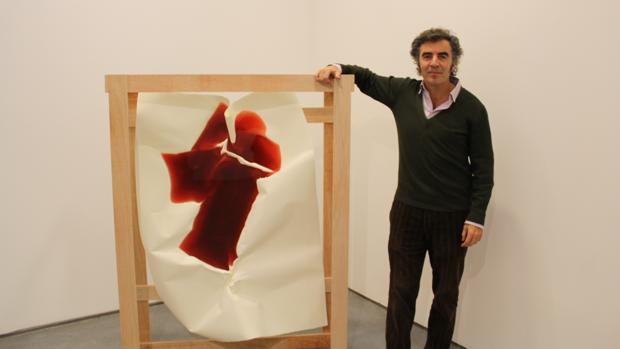 El galerista Alberto de Juan junto a una pieza de la serie «Lagos», del artista Miler Lagos