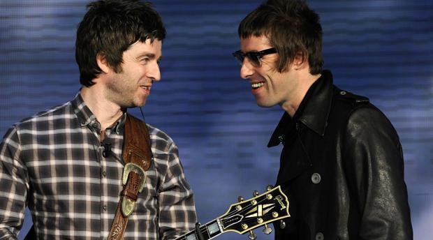 Los hermanos Gallagher, de Oasis, sonriéndose en medio de un concierto
