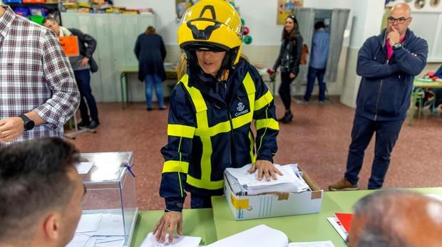Una trabajadora postal de Correos entrega votos por corresos en la mesa de un colegio electoral de Toledo