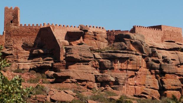 Silueta del castillo de Peracense, mimetizado con la rojiza mole de roca sobre la que se asienta