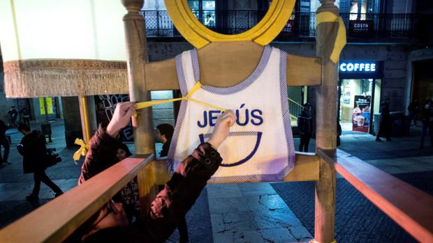 Un miembro de los CDR colocando lazos en el pesebre de Plaza San Jaime