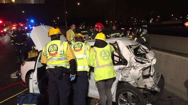Los bomberos y efectivos de emergencias tratan de liberar del taxi al conductor y a la pasajera