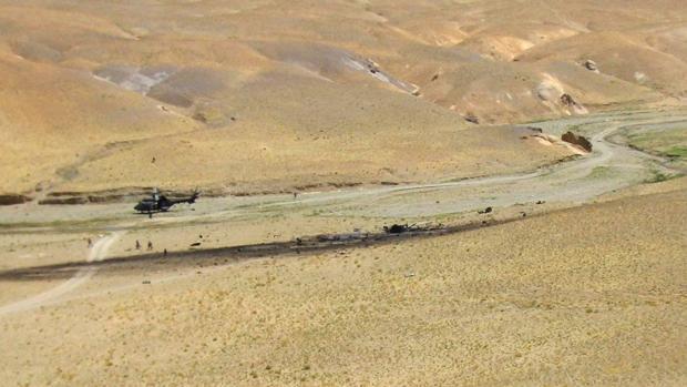 """Vista de los restos del helicóptero """"Cougar"""", que se estrelló en Afganistán cuando participaba en una operación de integración de las Fuerzas Armadas españolas, en el que fallecieron diecisiete militares españoles. A la izquierda el helicóptero medicalizado que acudió al lugar de los hechos"""