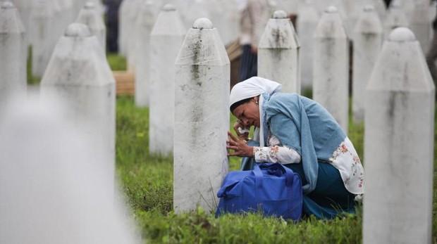 Una mujer llora junto a la tumba de un familiar en el centro memorial de Potočari