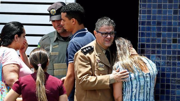 Un oficial de la Policia militar consuela a una mujer en el lugar de un tiroteo en una escuela de Brasil