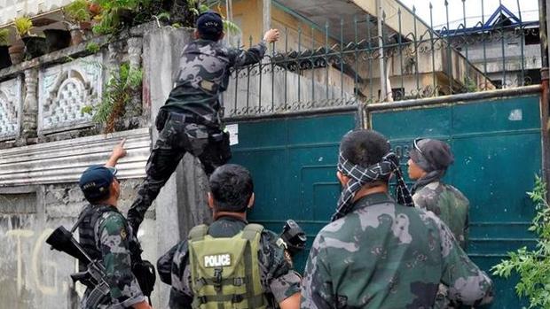 Soldados filipinos se disponen a registrar un domilicio