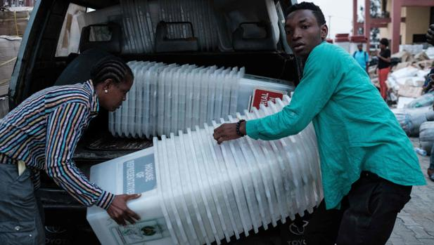 Miembros de la Comisión Electoral descargan unas urnas en Nigeria