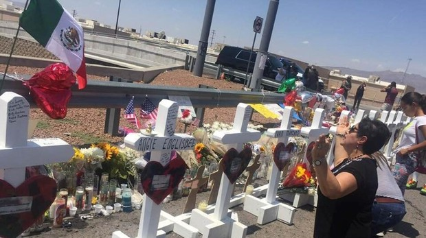 Una señora reza junto a las cruces que fueron colocadas frente a la tienda Walmart en El Paso