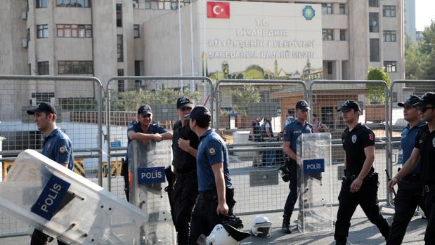 Agentes de la Policía turca caminan frente a la sede municipal de Diyarbakir, hoy