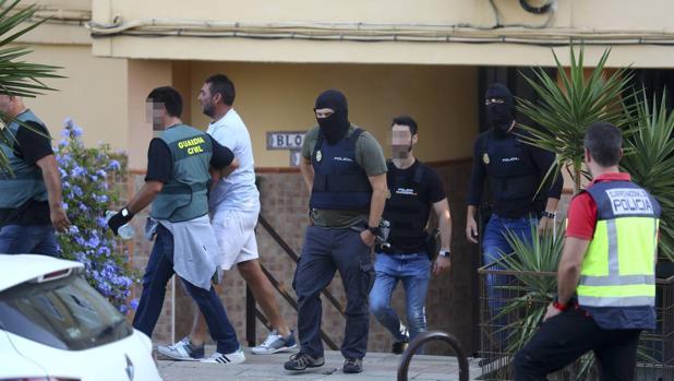 Policías y guardias civiles se llevan a uno de los detenidos tras un registro.