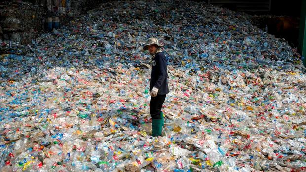 Un trabajador de un vertedero, rodeado de botellas de plástico